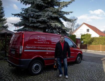 Person mit schwarzer Jacke vor einem roten Firmenfahrzeug
